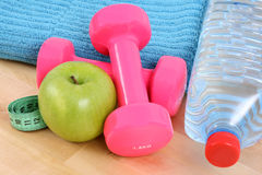 Sports equipment. Dumbbells water and green apple Stock Photos