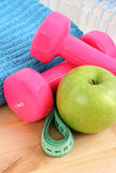 Sports equipment. Dumbbells water and green apple Royalty Free Stock Photo