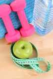 Sports equipment. Dumbbells water and green apple stock photography