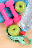 Sports equipment. Dumbbells water and green apple stock image