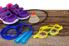 Sports equipment birdie is on the racket, skipping rope, swimming goggles and sneakers Royalty Free Stock Photos