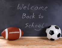 Sports equipment with black chalkboard in background. Football and soccer ball on desktop. Erased black chalkboard in background along with welcome back to stock image