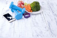 Sports equipment, blue dumbbells and fruits, vegetables and telephone. Fitness bracelet and headphones for music. Free space for. Writing text or advertising Royalty Free Stock Images