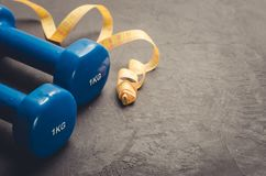 Sports equipment on dark background/ Blue dumbbells and yellow centimeter against a dark background. Copy space stock images