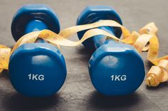Sports equipment on a dark background/ Sports equipment with Blue dumbbells and yellow measuring tape. Selective focus stock photo