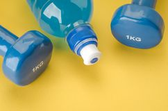 Sports equipment with dumbbells and bottle/blue dumbbells and bo royalty free stock image