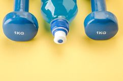 Sports equipment with dumbbells and bottle/blue dumbbells and bottle on a yellow background. Copy space. Top view stock photos