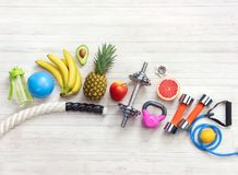 Sports equipment and healthy food on a white wooden background. Top view. Motivation Stock Images