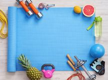 Sports equipment and healthy food on a white wooden background. Royalty Free Stock Image
