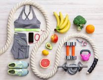Sports equipment and healthy food on a white wooden background. Stock Image