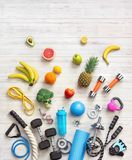 Sports equipment and healthy food on a white wooden background. Royalty Free Stock Images