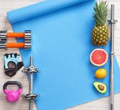 Sports equipment and healthy food on a white wooden background. Top view. Motivation Royalty Free Stock Photo