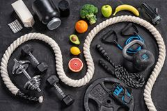 Sports equipment and healthy nutrition on a black background. Top view. Motivation Royalty Free Stock Images