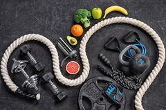 Sports equipment and organic food on a black background. Top view. Motivation Royalty Free Stock Photos