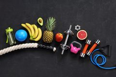 Sports equipment and organic food on black background. Top view. Motivation Royalty Free Stock Photo
