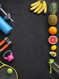 Sports equipment and organic food on black background. Top view. Motivation stock image