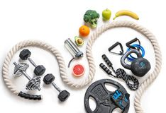 Sports equipment and organic food on a white background. Top view. Motivation Stock Photography