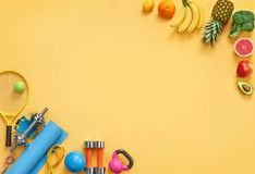 Sports equipment and organic food on yellow background. Top view. Motivation. Copy space Stock Image