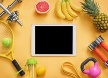 Sports equipment and organic food on yellow background. Top view. Motivation Stock Images