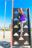 Sports equipment in the park. Rope and climbing ladder.Young woman on a climbing ladder Stock Photos