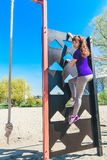 Sports equipment in the park. Rope and climbing ladder.Young woman on a climbing ladder Royalty Free Stock Photo