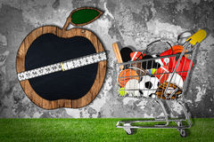 Sports equipment shopping cart stone wall apple Royalty Free Stock Photo