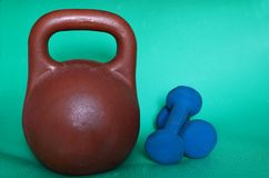 Sports equipment. Weight sports and dumbbells. Sports equipment. Brown weight sports and blue dumbbells on green background. Make your body better Stock Photo