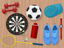 Sports equipment on wooden floor. Shoes, darts, water and dumbbells.