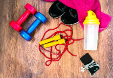 Sports equipment on the wooden floor with sneakers, telephone Royalty Free Stock Image