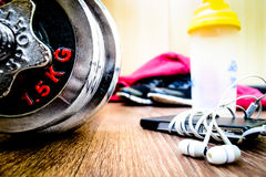 Sports equipment on the wooden floor with sneakers, telephone Stock Photography