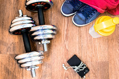 Sports equipment on the wooden floor with sneakers, telephone Stock Images