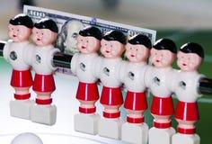 Sports et concept d'argent - les joueurs de football de jouet se tiennent dans le domaine et le billet de banque en cent dollars  Image libre de droits