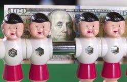 Sports et concept d'argent - les joueurs de football de jouet se tiennent dans le domaine et le billet de banque en cent dollars  Photos stock