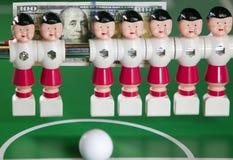 Sports et concept d'argent - les joueurs de football de jouet se tiennent dans le domaine et le billet de banque en cent dollars  Image stock
