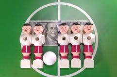 Sports et joueurs de football de concept-jouet d'argent dans le domaine et le billet de banque en cent dollars sur un fond Images libres de droits