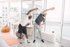 Positive sporty men doing physical activities. Sports exercise. Positive sporty men standing together while doing physical activities Royalty Free Stock Images
