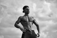 Sports exercises for men. Sexy muscular man on sky background. Sports exercises for men. young macho man model athlete with muscular sexy body and bare chest Royalty Free Stock Photography
