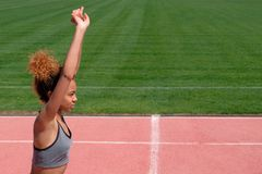 Sports exercises and stretching or preparing a runner to start at the stadium. A young beautiful African-American girl in a gray T stock image