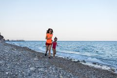 Sports family: morning jogging along the beach. Mom and daughter run along the beach. Sea active beautiful blue child free space fun girl happy holiday kid royalty free stock photography