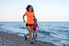Sports family: morning jogging along the beach. Mom and daughter run along the beach active attractive beautiful beauty blue body free space girl happiness stock image