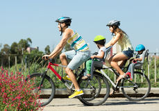 Sports family. Traveling on bicycles with children in baby bicycle seats Royalty Free Stock Photography