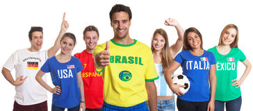 Sports Fan from Brazil showing thumb up with other fans Stock Photo