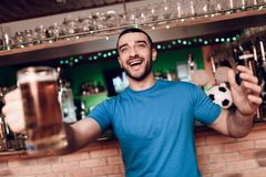 Sports fan celebrating goal for their team and cheering at sports bar. He`s supporting blue team Stock Photos
