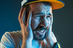 Sports, emotions and fan people concept - sad man watching sports on tv and supporting team at home. Sports, fan human emotions and people concept - sad young Royalty Free Stock Photography