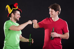 Sports fans with beer. Two fans of sport doing a fist bump holding bottles of beer Stock Image