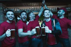 Sports fans celebrating and cheering in front of tv drinking beer at sports bar. They are supporting red team stock photography