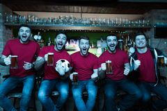 Sports fans celebrating and cheering in front of tv drinking beer at sports bar. stock image