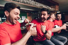Sports fans celebrating goal for their team and cheering at sports bar. They are supporting red team royalty free stock image