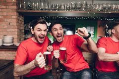 Sports fans celebrating goal for their team and cheering at sports bar. They are supporting red team stock photos