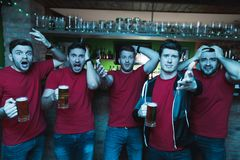 Sports fans shouting sad in front of tv drinking beer at sports bar. They are supporting red team stock image